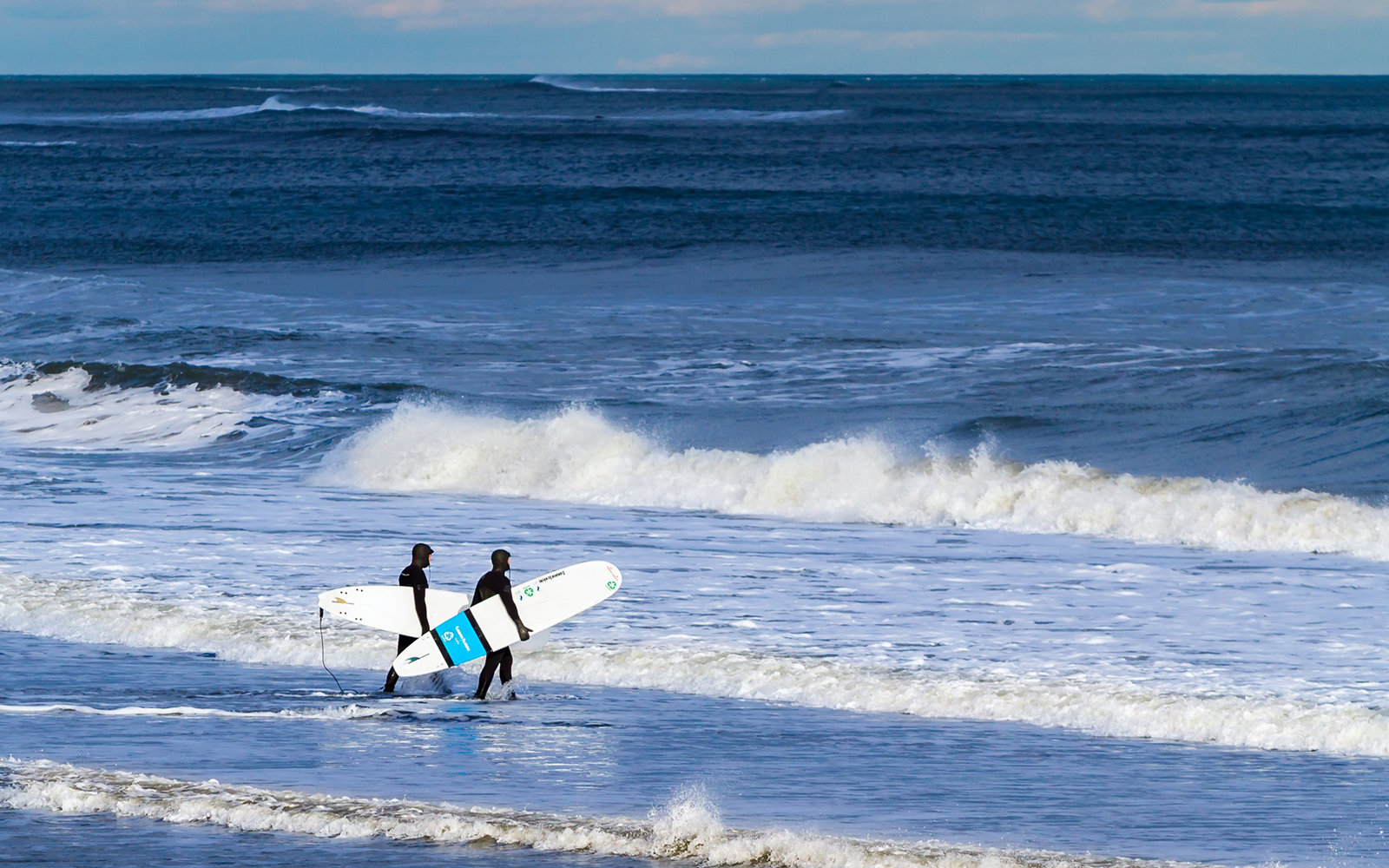 Two men in wetsuits with surfboards entering the surf at Hampton Beach New Hampshire