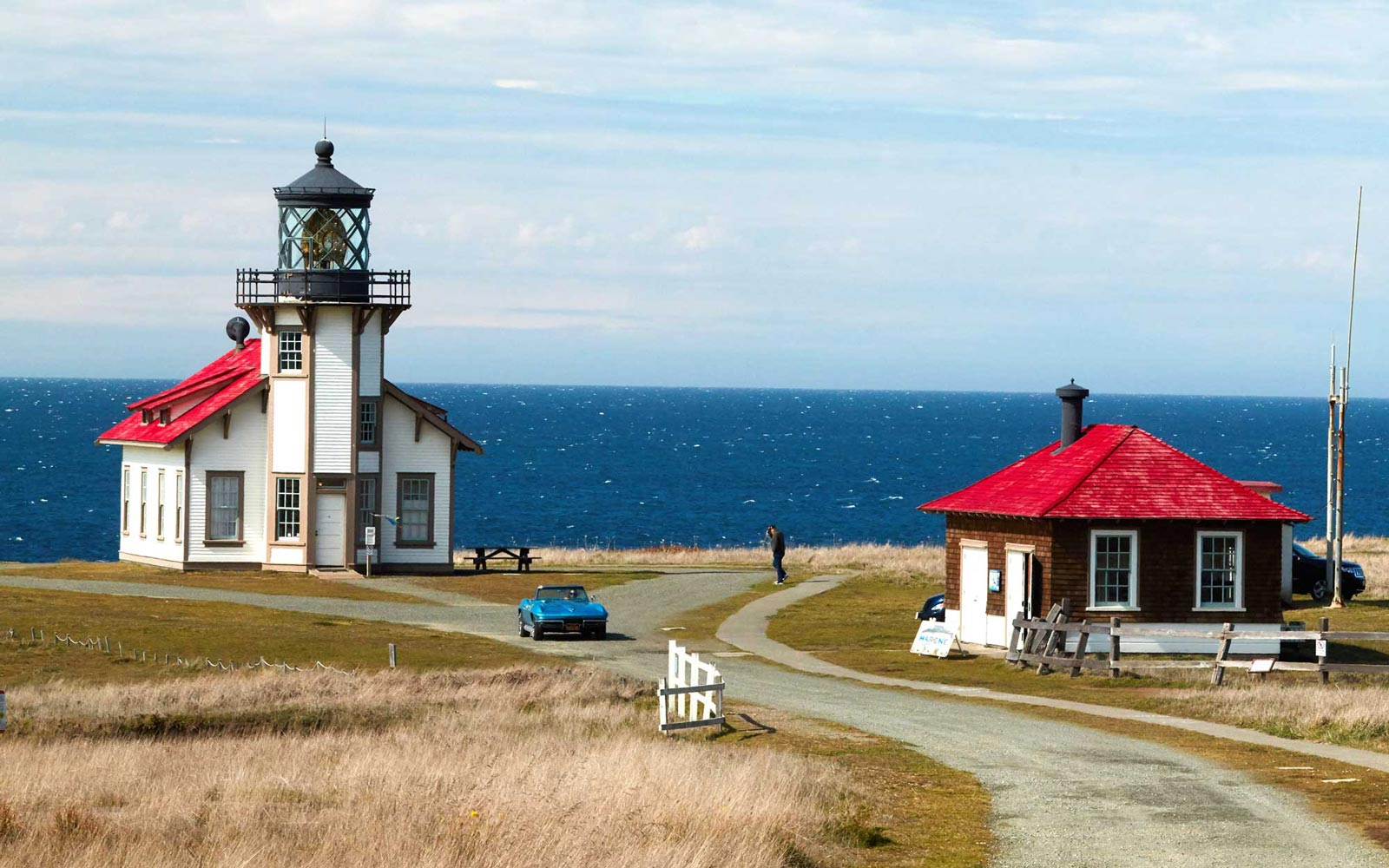 Vintage car driving past the Point Cabrillo Light Station, outside of Mendocino, California