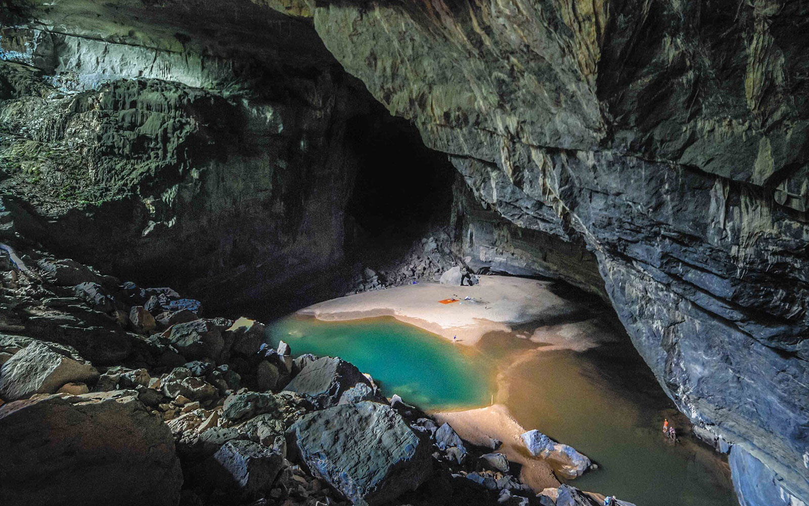 Before reaching Son Doong itself, the trek passes through the colossal Hang En cave. After wading though a river and then climbing a massive hill of boulders, trekkers are met with this view. On the beach below a fire burns and tents are set up for the first night of camping.