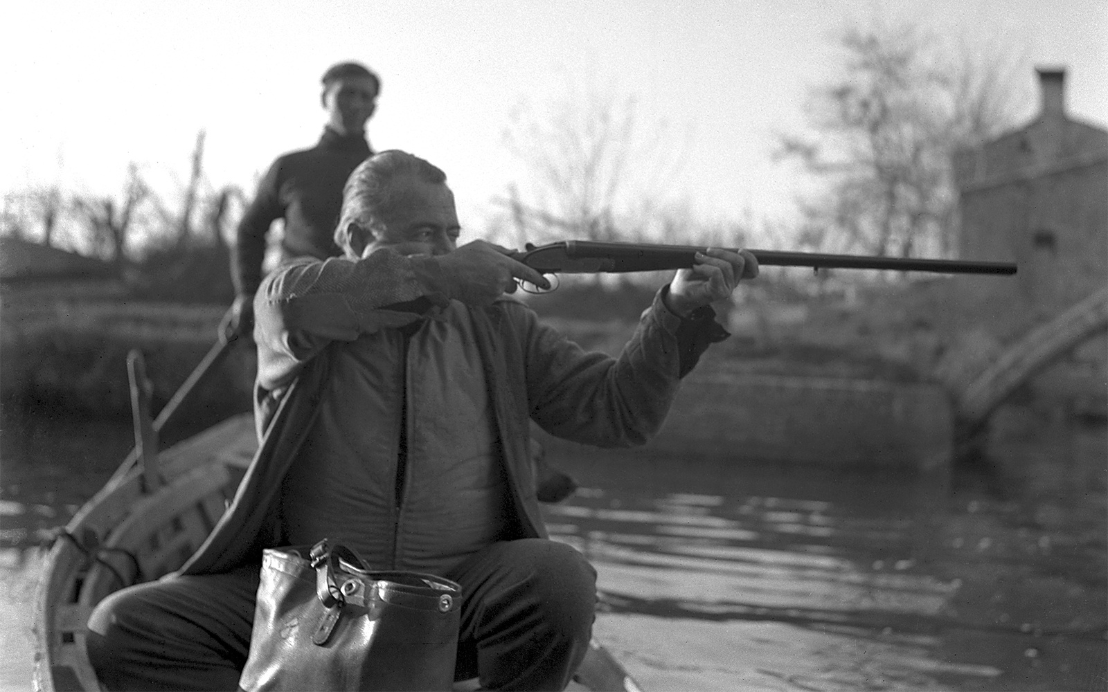 American writer Ernest Hemingway, sitting on a boat, taking aim while hunting ducks in a pond, on Torcello island, Venice, 1948. Hemingway is using a shotgun by James Purdey & Sons. (Photo by Archivio Cameraphoto Epoche/Getty Images)