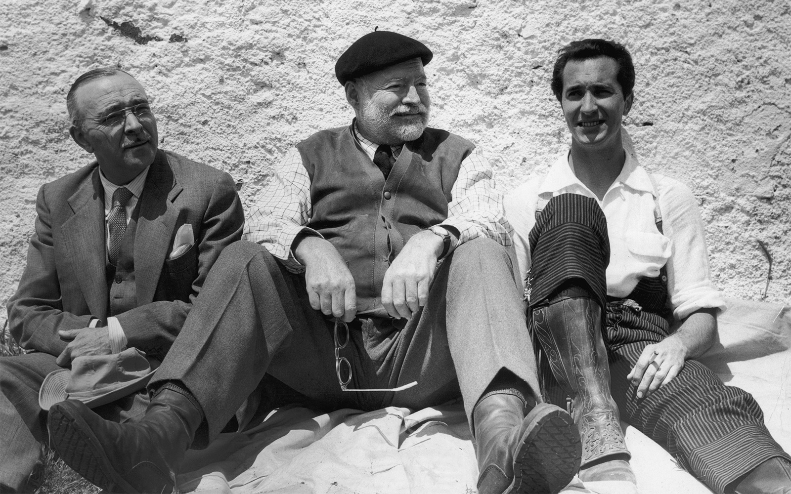 circa 1959:  American author Ernest Hemingway (1899 - 1961; (centre) and Spanish bullfighter Luis Dominguin (right; smoking a cigarette, sit against a wall, Spain.  (Photo by Hulton Archive/Getty Images)