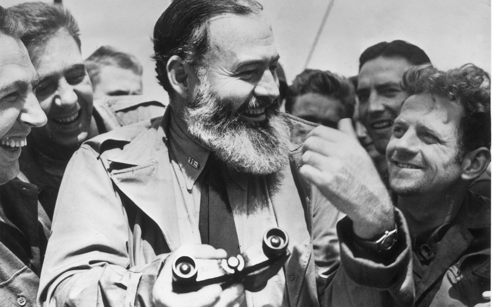 1944:  American writer Ernest Hemingway (1899 - 1961) travelling with US soldiers, in his capacity as war correspondent,  on their way to Normandy for the D-Day landings.  (Photo by Central Press/Getty Images)