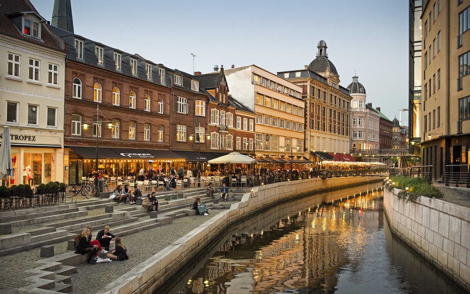 People relaxing at Aarhus river at dusk