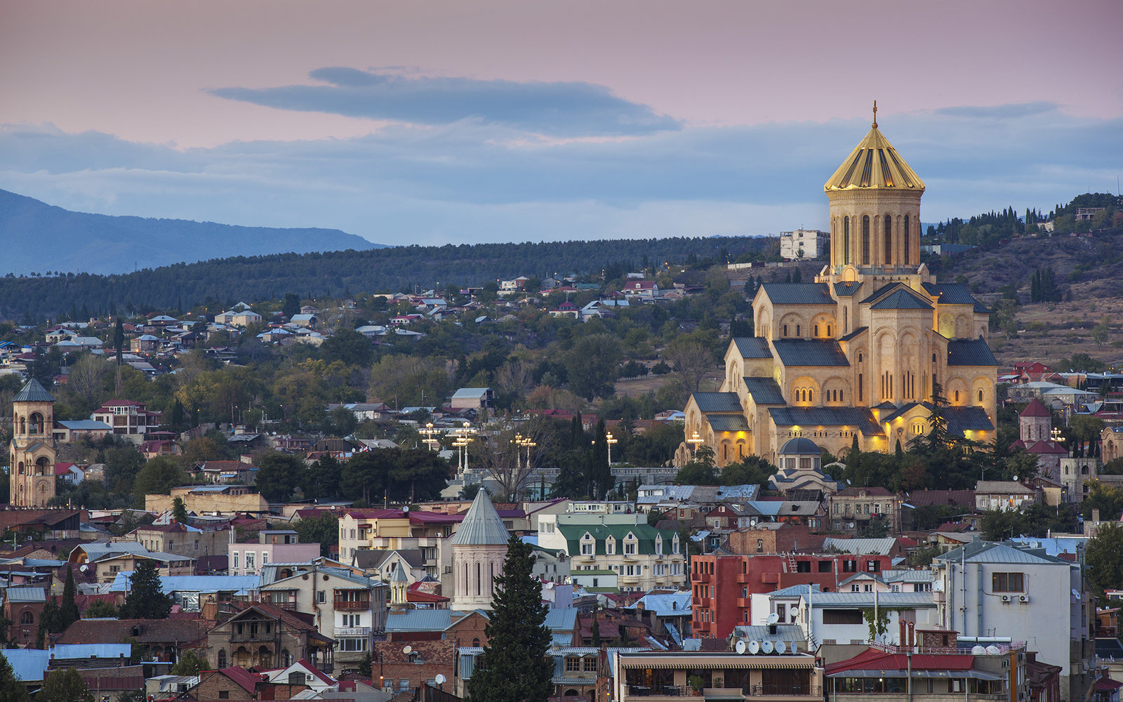 Georgia, Tbilisi, City and Tsminda Sameba Cathedral at dusk