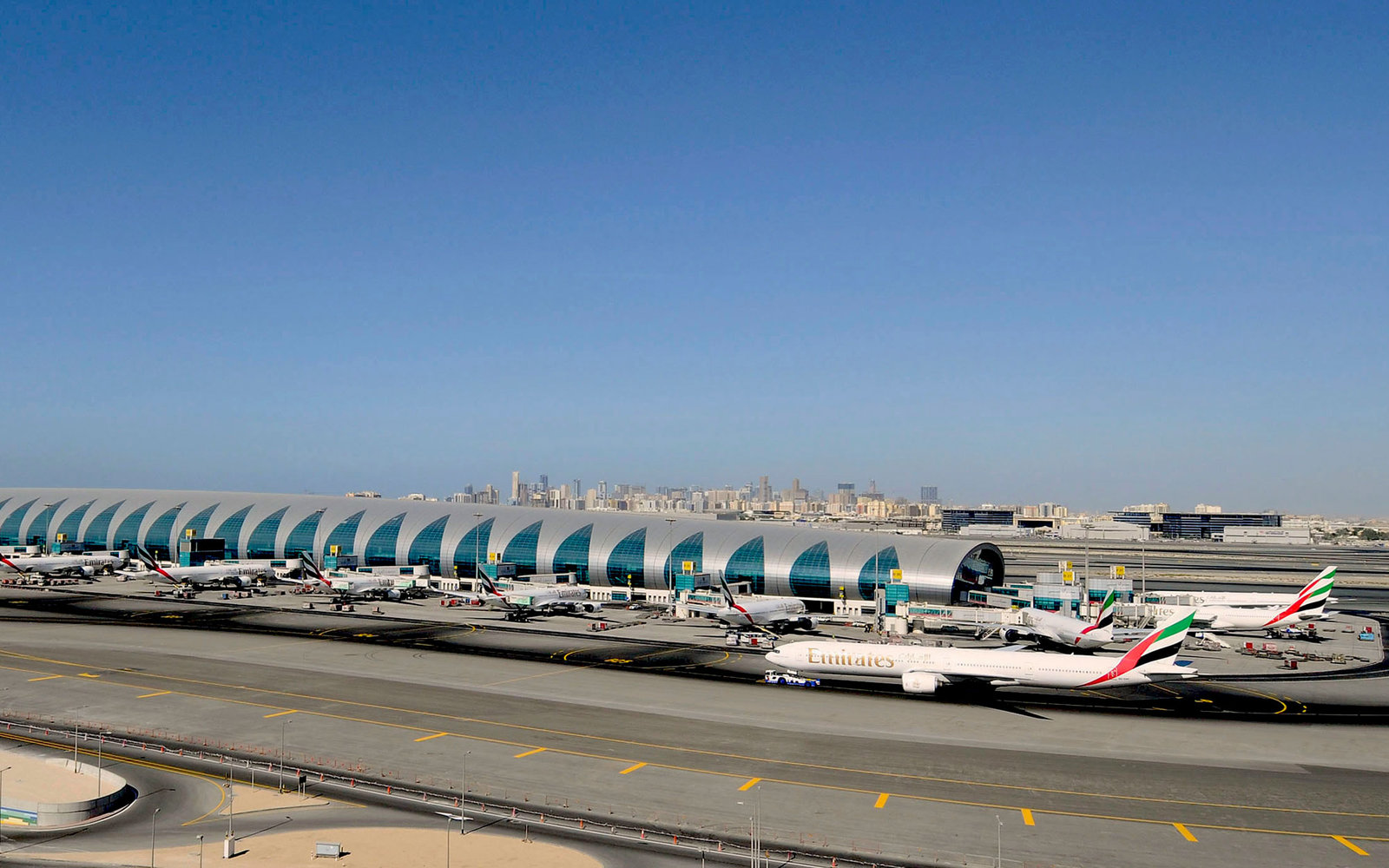 An Emirates airplane taxis down the runway at the Dubai International Airport in Dubai, United Arab Emirates, on Tuesday, Nov. 24, 2009. Dubai, whose government and state-owned companies borrowed $80 billion to fund an economic boom, raised $5 billion by