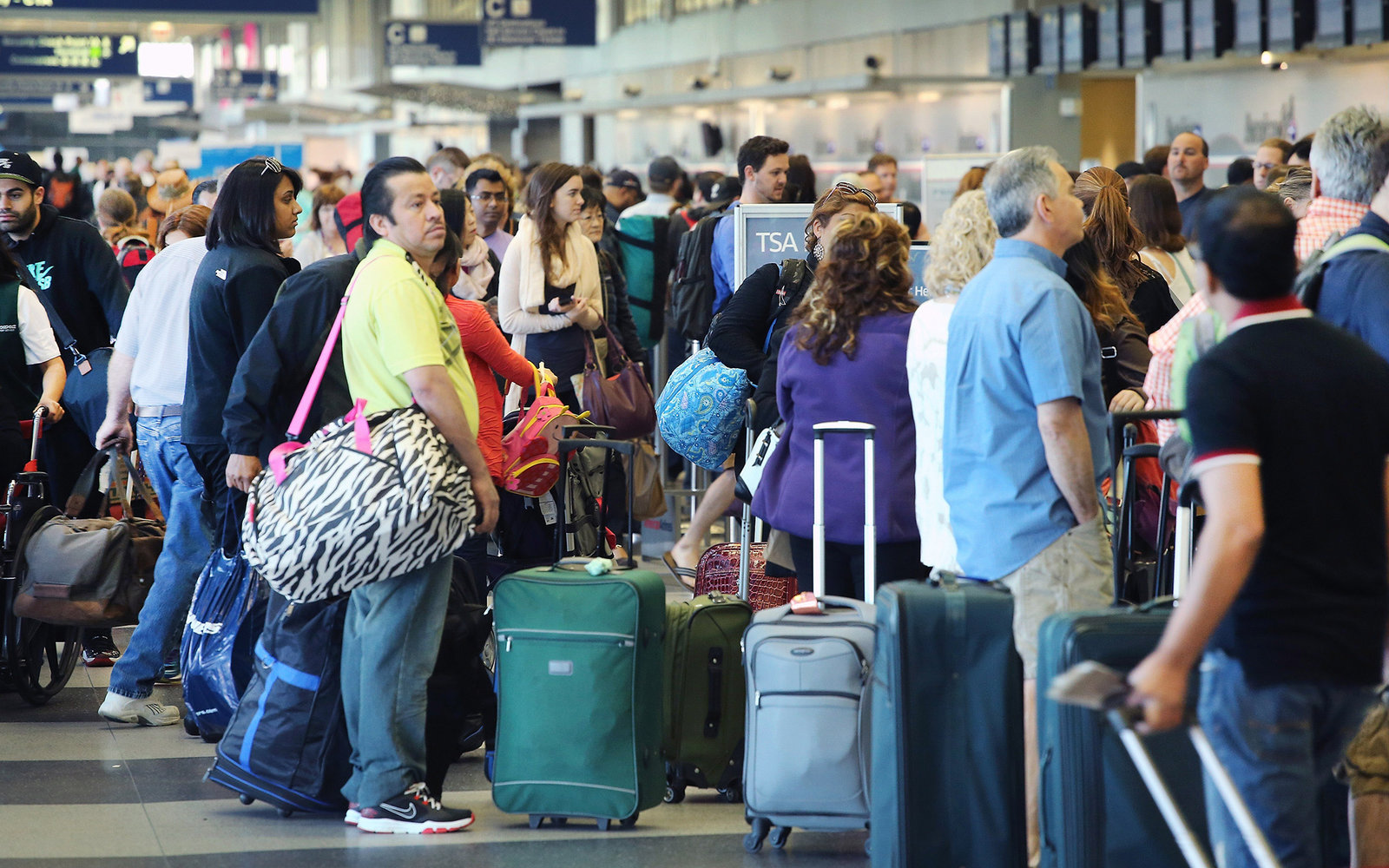 CHICAGO, IL - MAY 23:  Passengers wait in line at a security checkpoint at O'Hare Airport May 23, 2014 in Chicago, Illinois. Chicago's O'Hare and Midway International Airports expect 1.5 million passengers over a six-day travel period covering Memorial Da