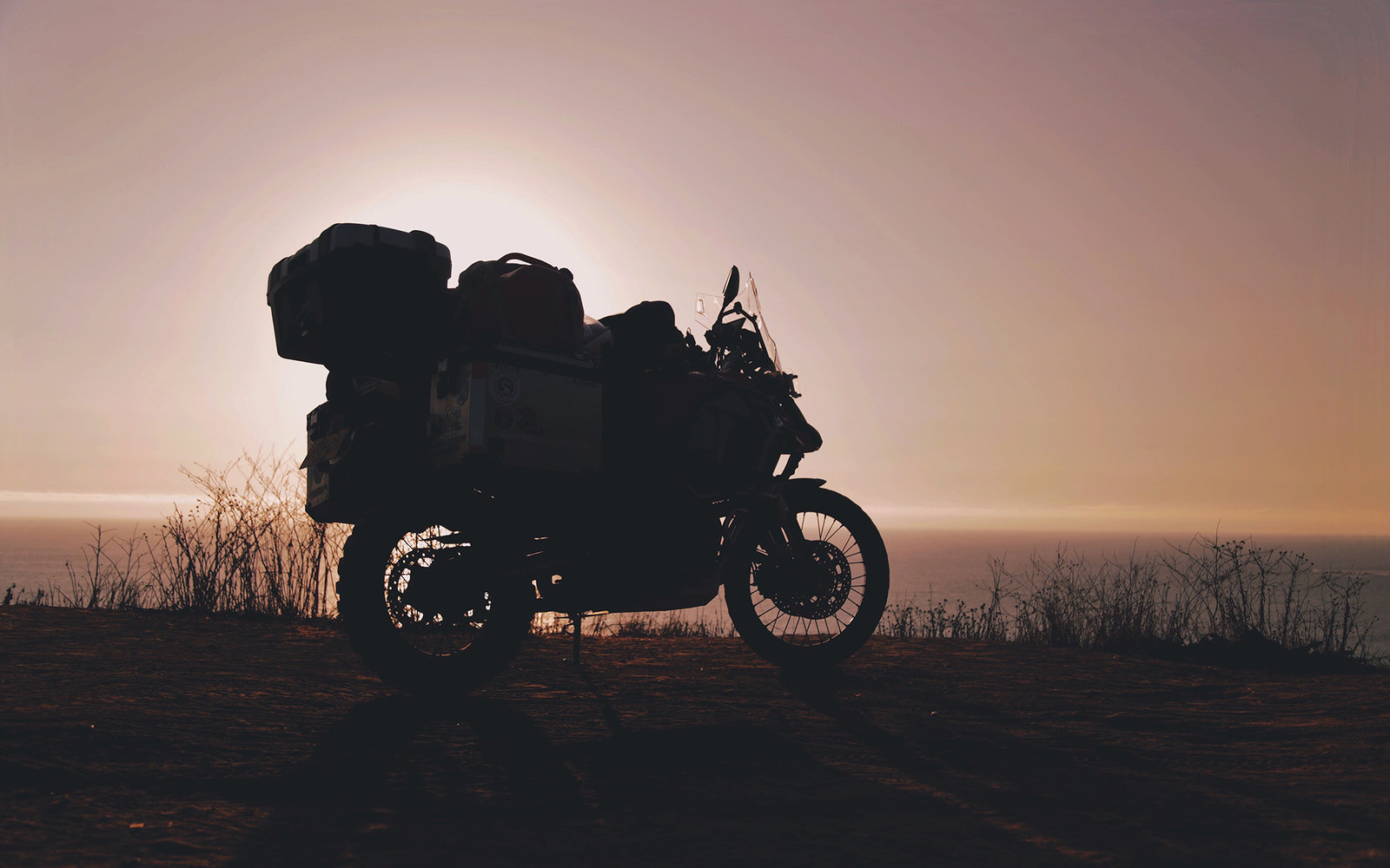 Silhouette Motorcycle Parked By Sea Against Sky During Sunset