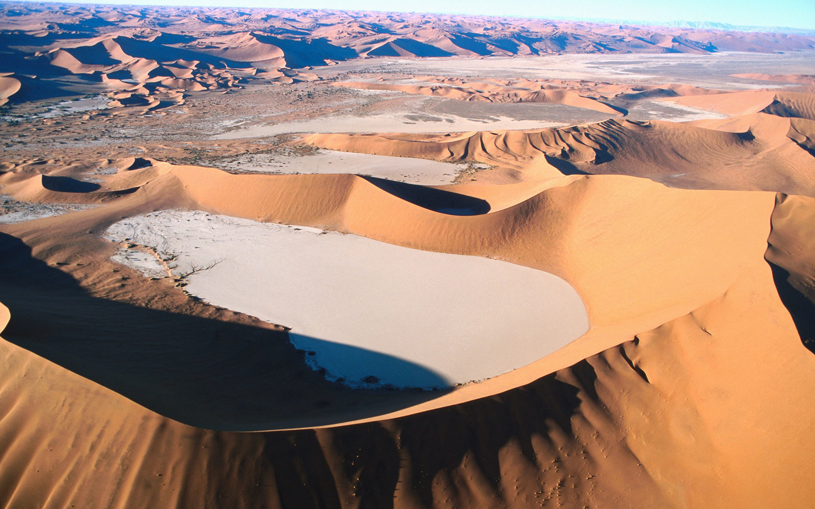 Aerial of natural basin between sand dunes in Namib Desert Park.