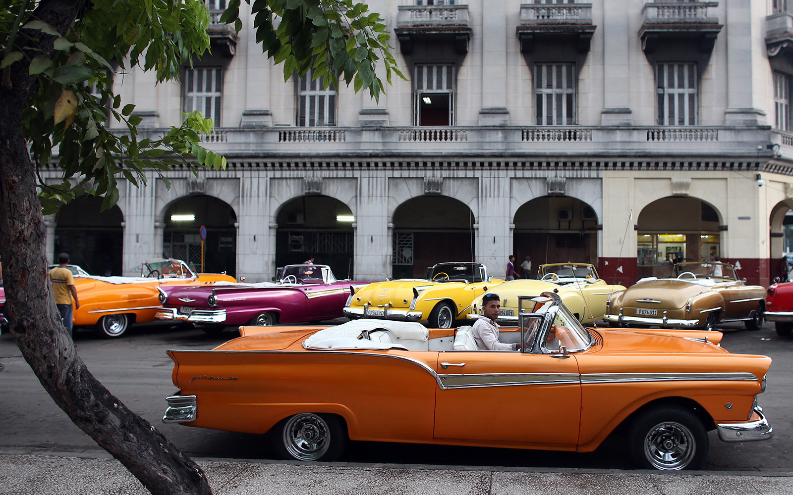 HAVANA, CUBA - SEPTEMBER 16: A taxi driver sits in a vintage American car on September 16, 2015 in Havana, Cuba.  Pope Francis is due to make a three day visit to Cuba from September 19 where he will meet President Raul Castro and hold Mass in Revolution