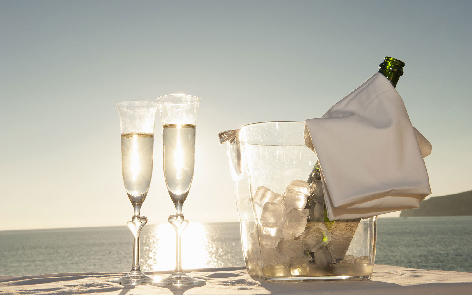 Champagne flutes and bucket against sunset