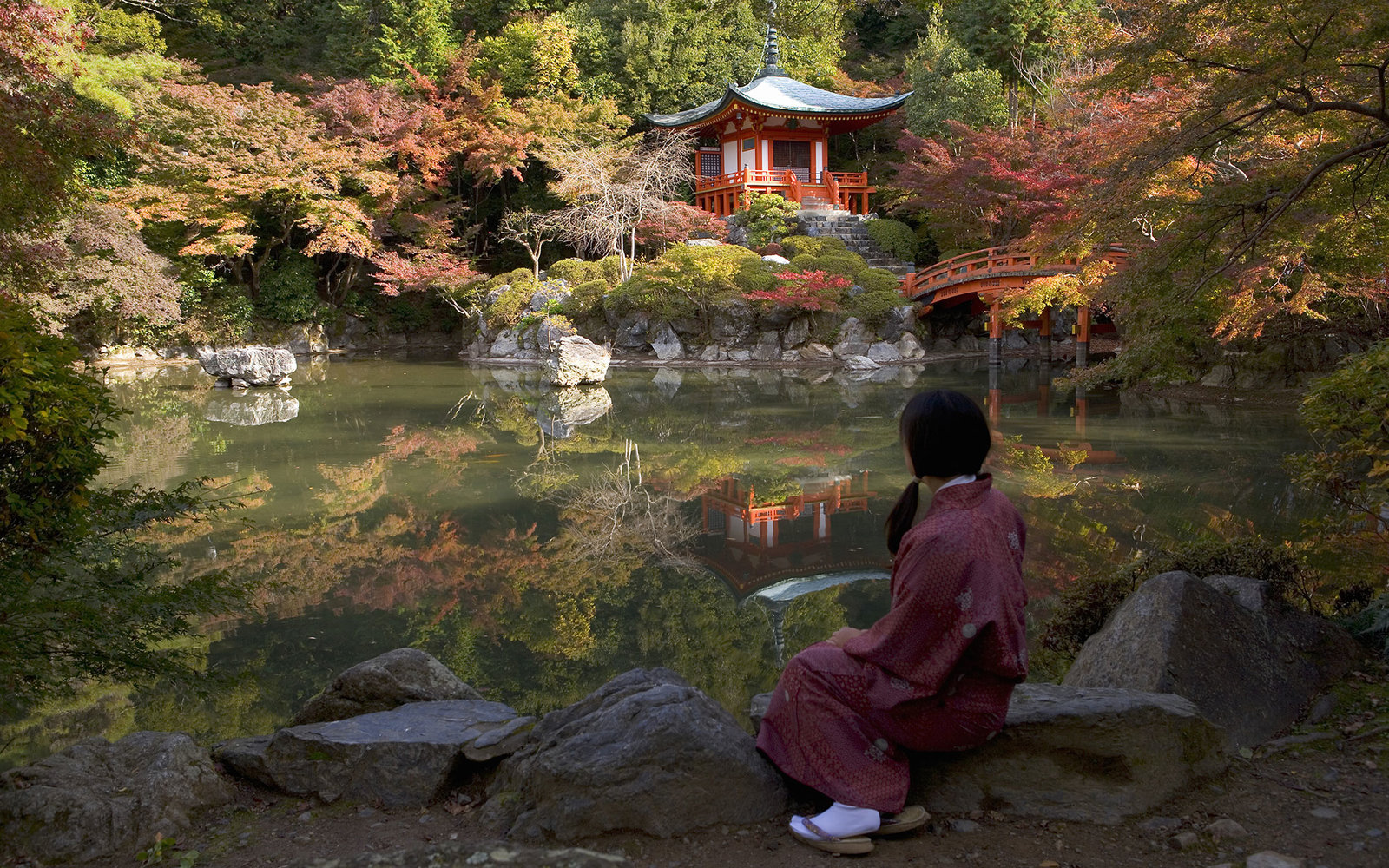 Japan, Kyoto, Daigo-ji Temple, woman on rock by pond, rear view