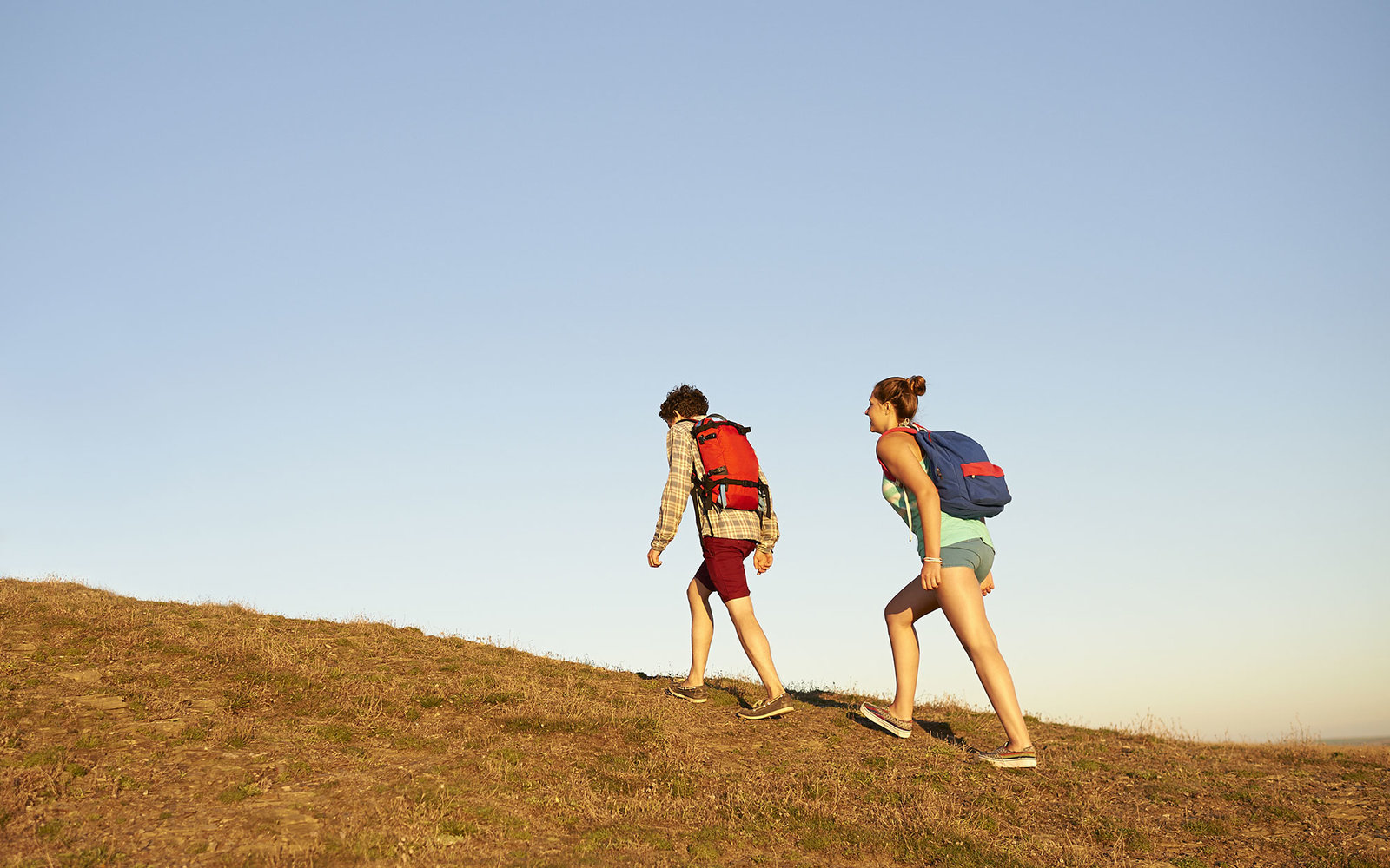 Couple hiking up hill in countryside.