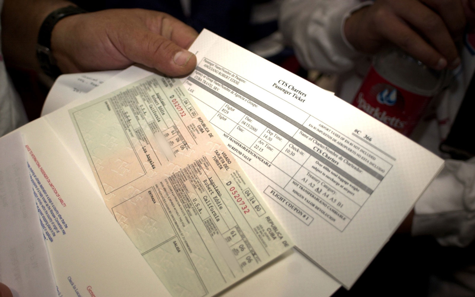 N367736 03: A Passenger Holds His Visa And Tickets To Board Flight 8529 From Los Angeles To Havana, Cuba At Los Angeles International Airport April 15, 2000. Taca Airlines Will Provide The First Regular Service To Havana From Los Angeles In Forty Years.