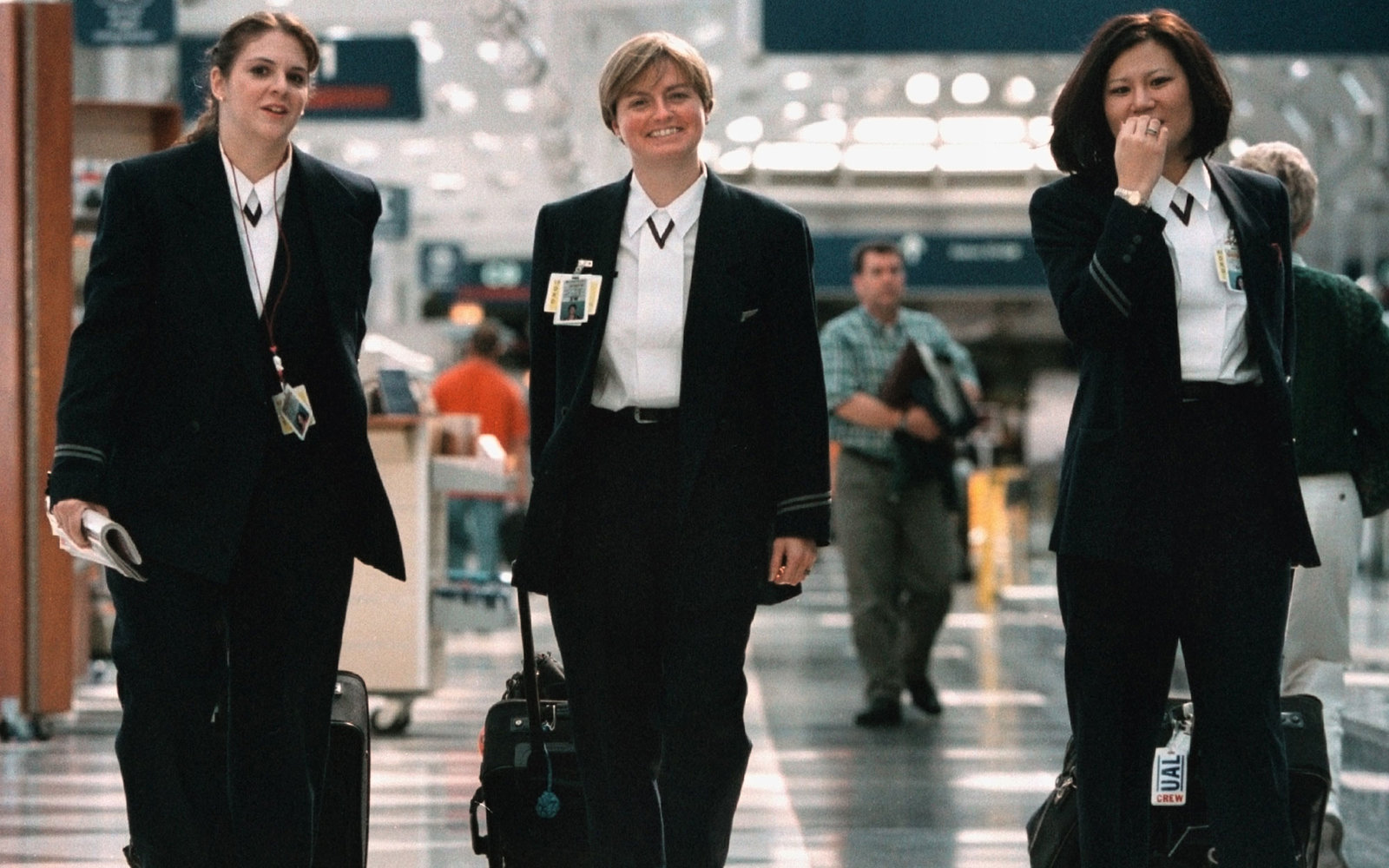 379263 01: Three United Airlines flight attendants walk from their arriving flight September 27, 2000 at Chicago's O''Hare International Airport. (Photo by Tim Boyle/Newsmakers)