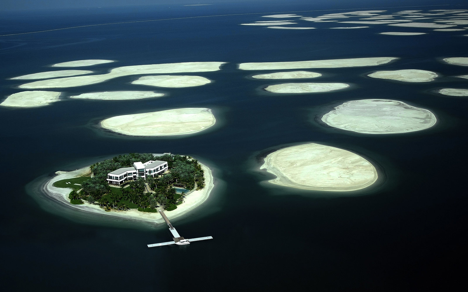 """(FILES) A picture taken on December 21, 2009 shows an aerial view of a cluster of man-made islands known as """"The World"""" by Emirati property developers Nakheel off the coast of Dubai. The real state project is stable, its developer Nakheel insists, despite"""