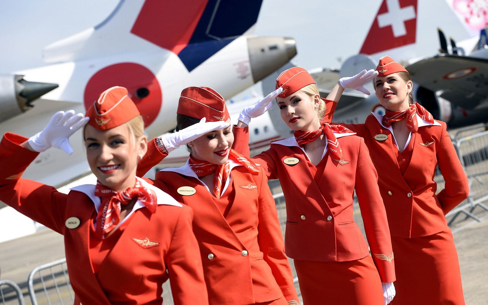 Cabin crew of the Russian airline Aeroflot salte as they walk past during the International Paris Airshow at Le Bourget on June 16, 2015.  AFP PHOTO /MIGUEL MEDINA        (Photo credit should read MIGUEL MEDINA/AFP/Getty Images)