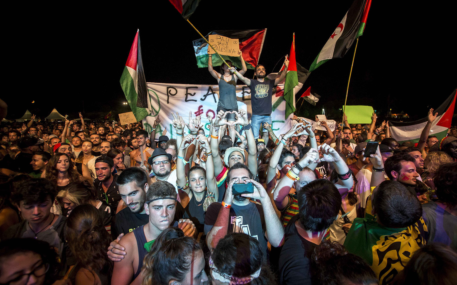 Revellers dance during a concert of Jewish American singer Matisyahu at the Rototom Sunsplash Reggae festival in Benicassim on August 22, 2015. Matisyahu confirmed his participation yesterday, two days after organisers apologised for pulling his show foll