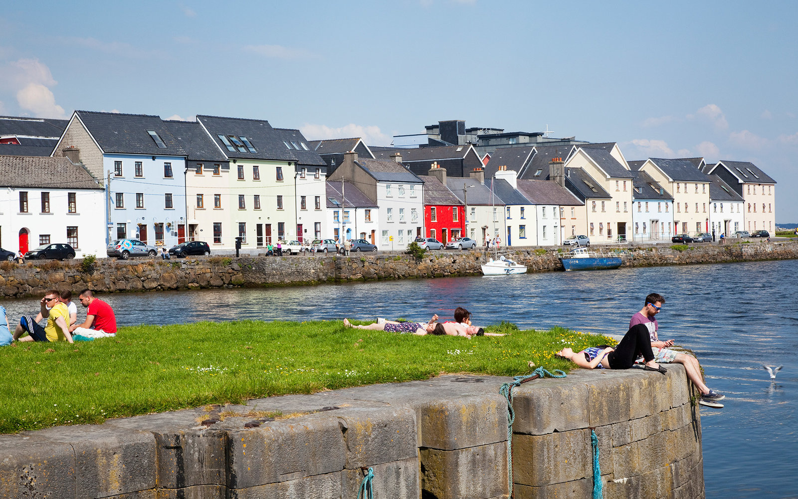 People sitting along the River Corrib in the Cladagh Area