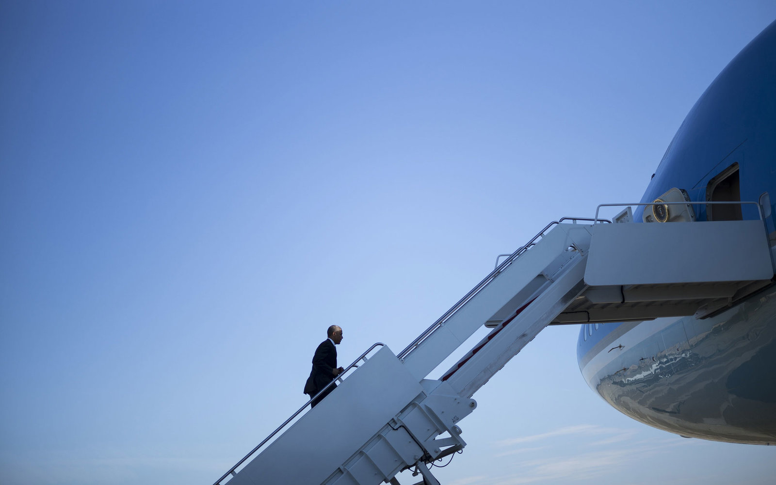 President Barack Obama boards Air Force One