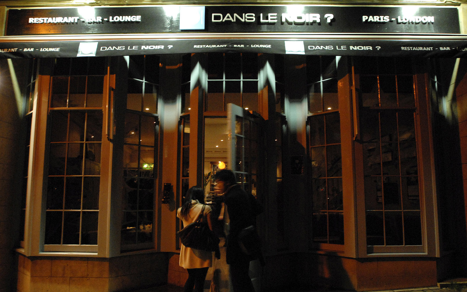 LONDON - OCTOBER 31:  Two patrons enter the restaurant Dans Le Noir? in London, England, on October 31, 2006. They are served dinner in complete darkness by blind servers. Patrons must rely on their server for everything, including bathroom breaks.  (Phot