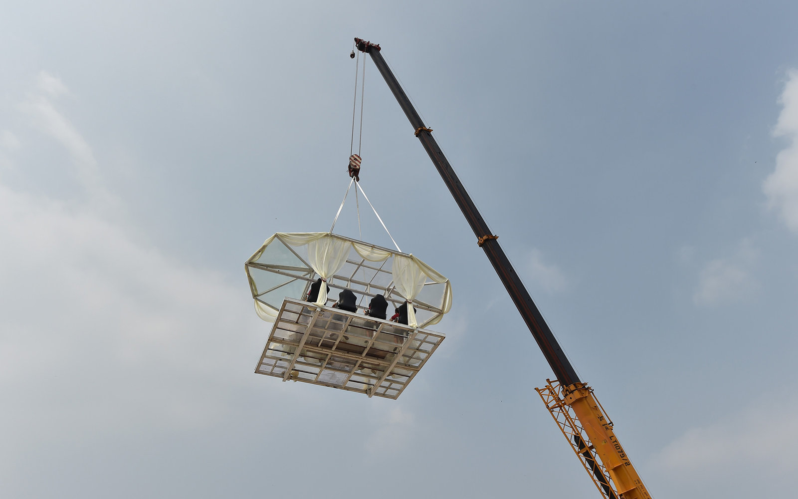 HEFEI, CHINA - SEPTEMBER 24: (CHINA OUT) People enjoy free launch at a dinner table lifted into sky by a crane on September 24, 2015 in Hefei, Anhui Province of China. The event is launched by Wanda Theme Park to celebrate the upcoming first anniversary o