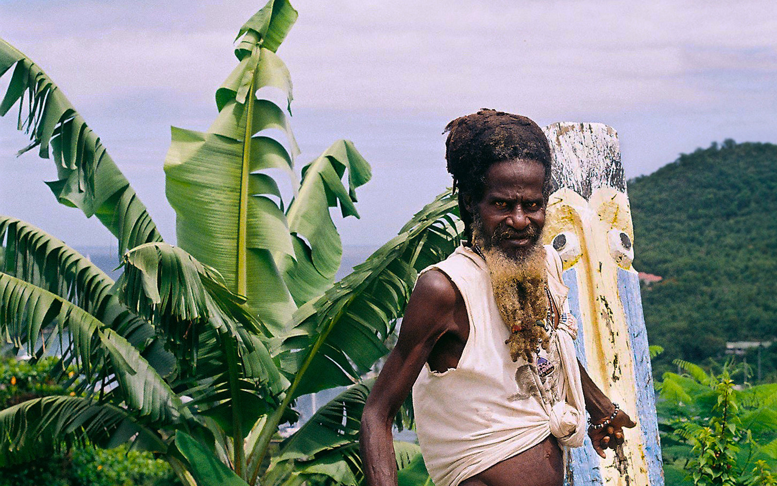 Caribbean culture. Taken in St. Lucia. When editing I focused on colour and composition, I have edited the sky in the background to make it a cooler blue than that of the foreground to add depth to my image. The male figure is off centre to portray him as