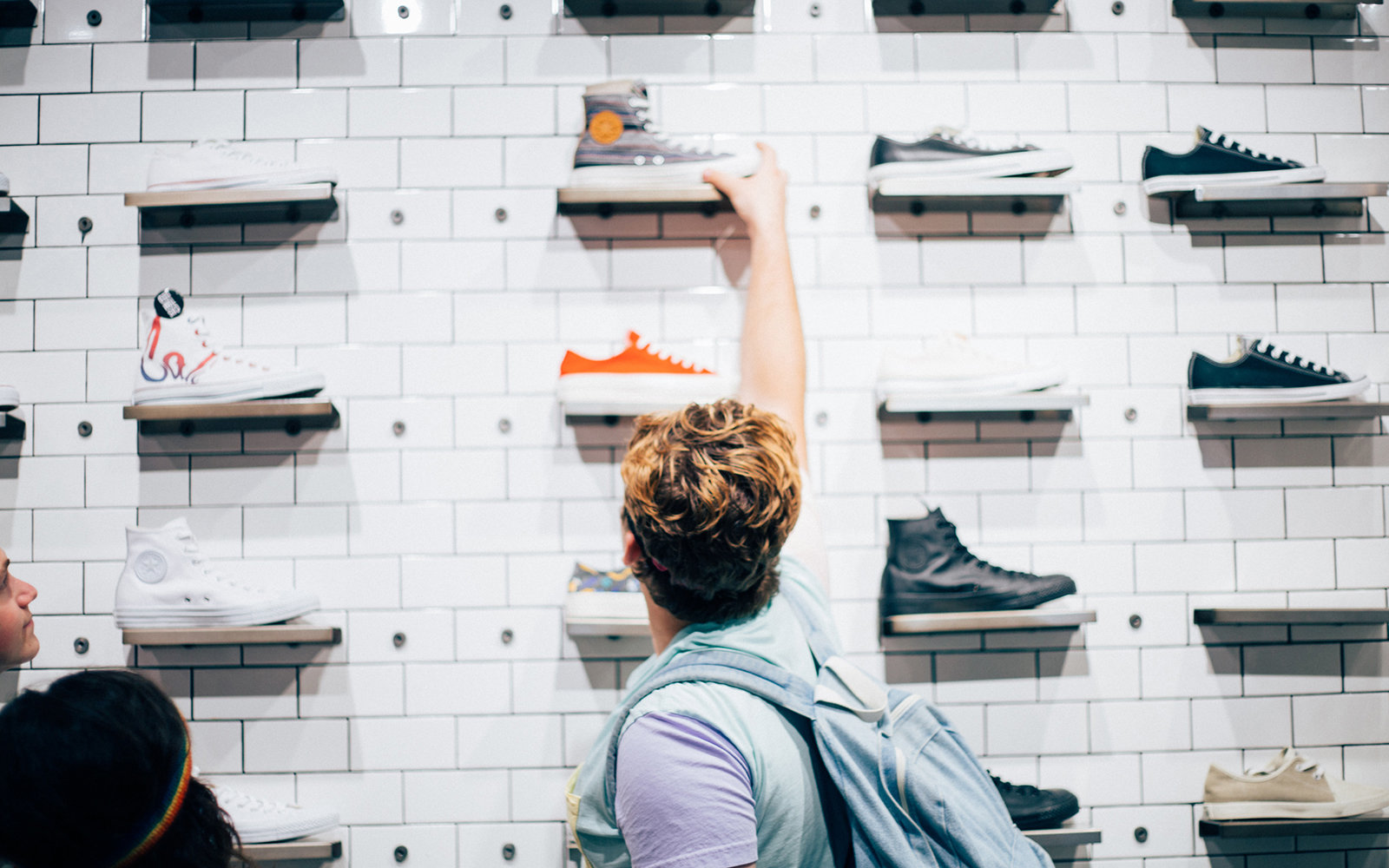 This photograph depicts a New Americana shoestore, a manifestation of today's youth popular culture in the United States, and shows a moment captured of an American teenager reaching up to that ideal of reinvented glamour.