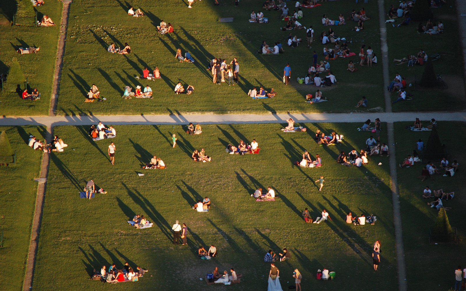 This photo was taken from the Eiffel Tower as the sun was setting, casting long shadows of the many people relaxing on the grass below.
