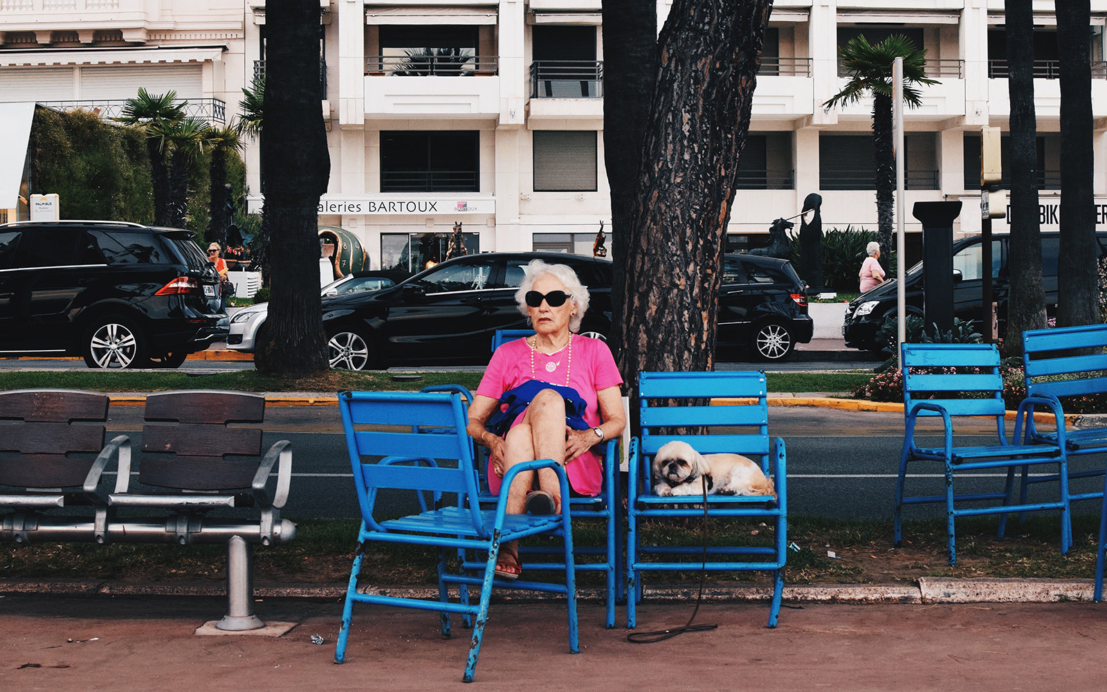Taken in Cannes, France 2015. I took this photograph on Promenade de la Croisette, during my summer holiday. Whilst everyone is mostly new wealth, this woman stood out, as she is relatively modest in appearance, and accompanied by a dog, as well as being