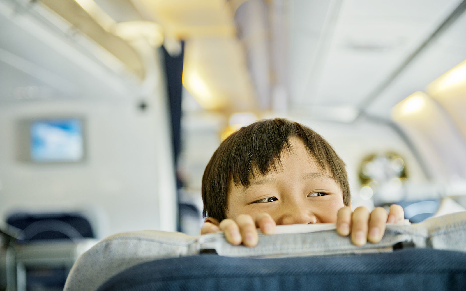Boy looking over business class seat of plane