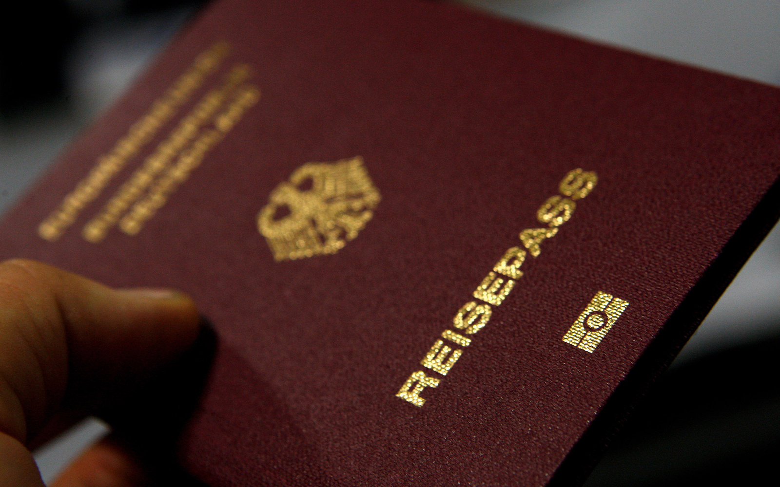FRANKFURT AM MAIN, GERMANY - OCTOBER 16:  A man holds up a passport with the EasyPass sign at the bottom during the presentation of the new automated border control system easyPass at Frankfurt International Airport on October 16, 2009 in Frankfurt am Mai
