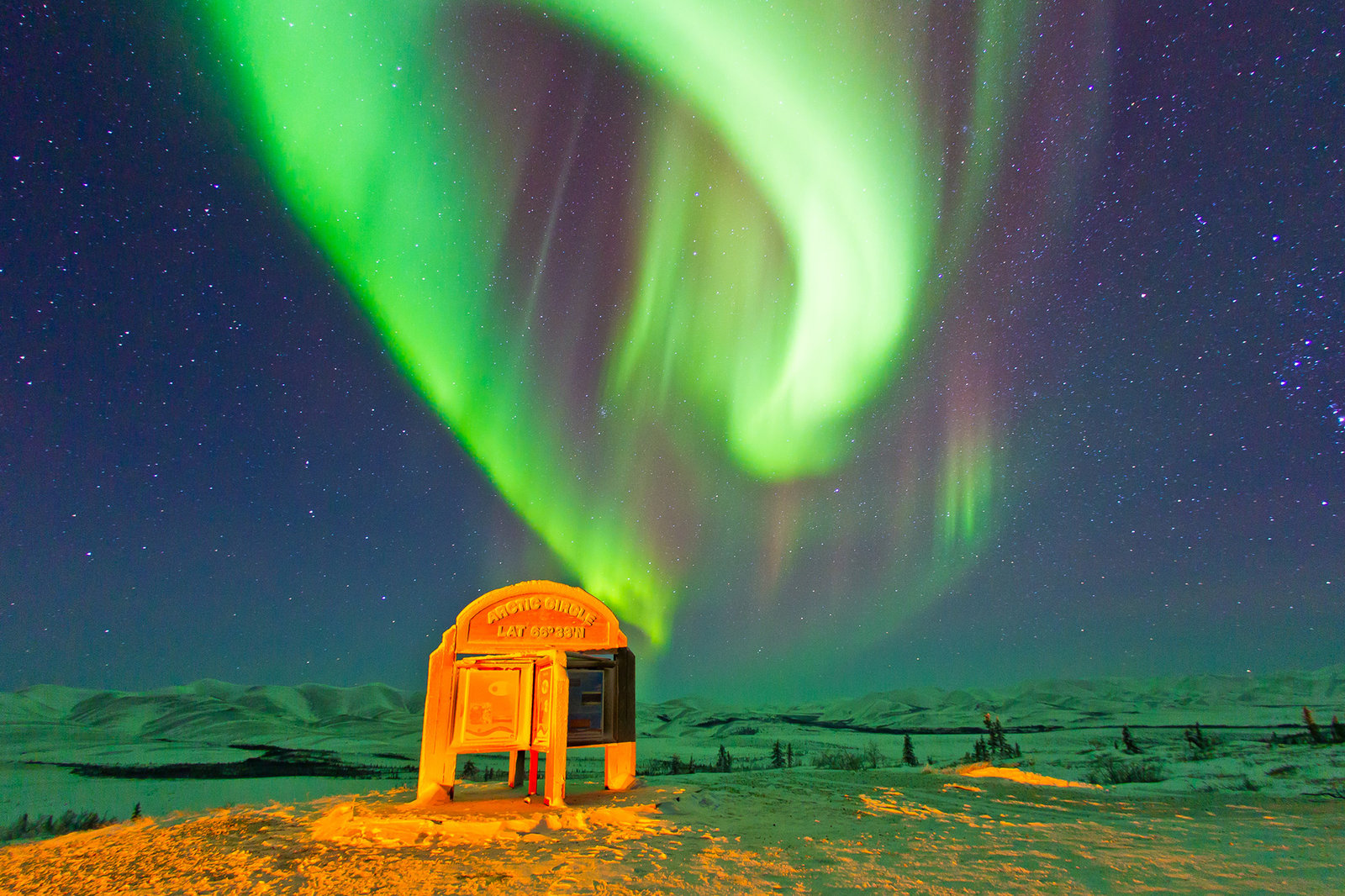 An aurora borealis in the arctic circle at the famous sign on the Dempster Highway. Also known as the Northern Lights is a natural light display in the sky in the high latitude (Arctic and Antarctic) regions, caused by the collision of energetic charged p