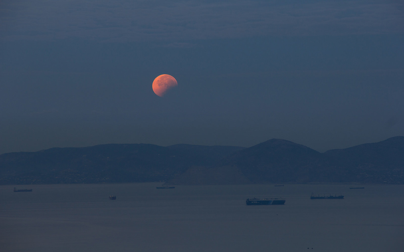ATHENS, GREECE - 2015/09/28: The moon sets over the sea with the shadow still visible. A total lunar eclipse took place while the moon was on its closest distance from earth, also known as supermoon. The phenomenon has happened only five times since 1900