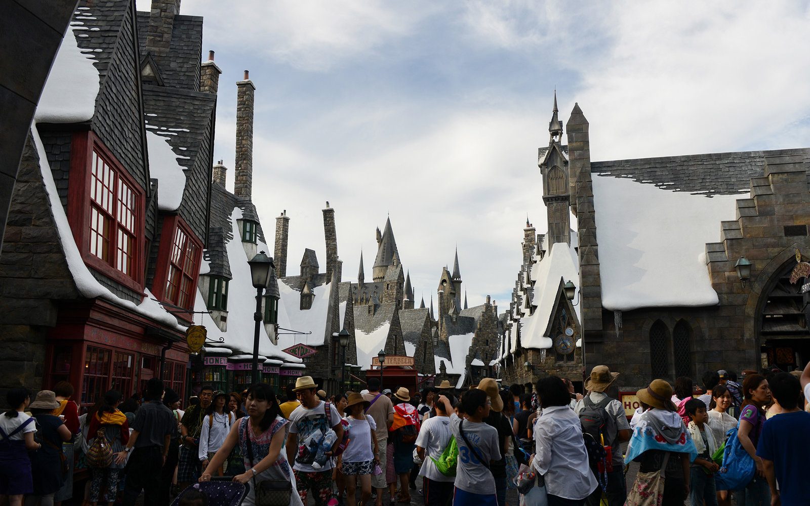 Visitors walk through The Wizarding World of Harry Potter themed area at Universal Studios Japan, operated by USJ Co., in Osaka, Japan, on Thursday, Aug. 7, 2014. USJ is counting on its cachet turning around a failing Universal Studios theme park in Japan