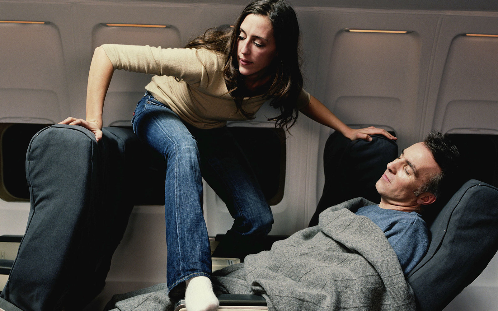 Young woman climbing over sleeping male passenger on aeroplane