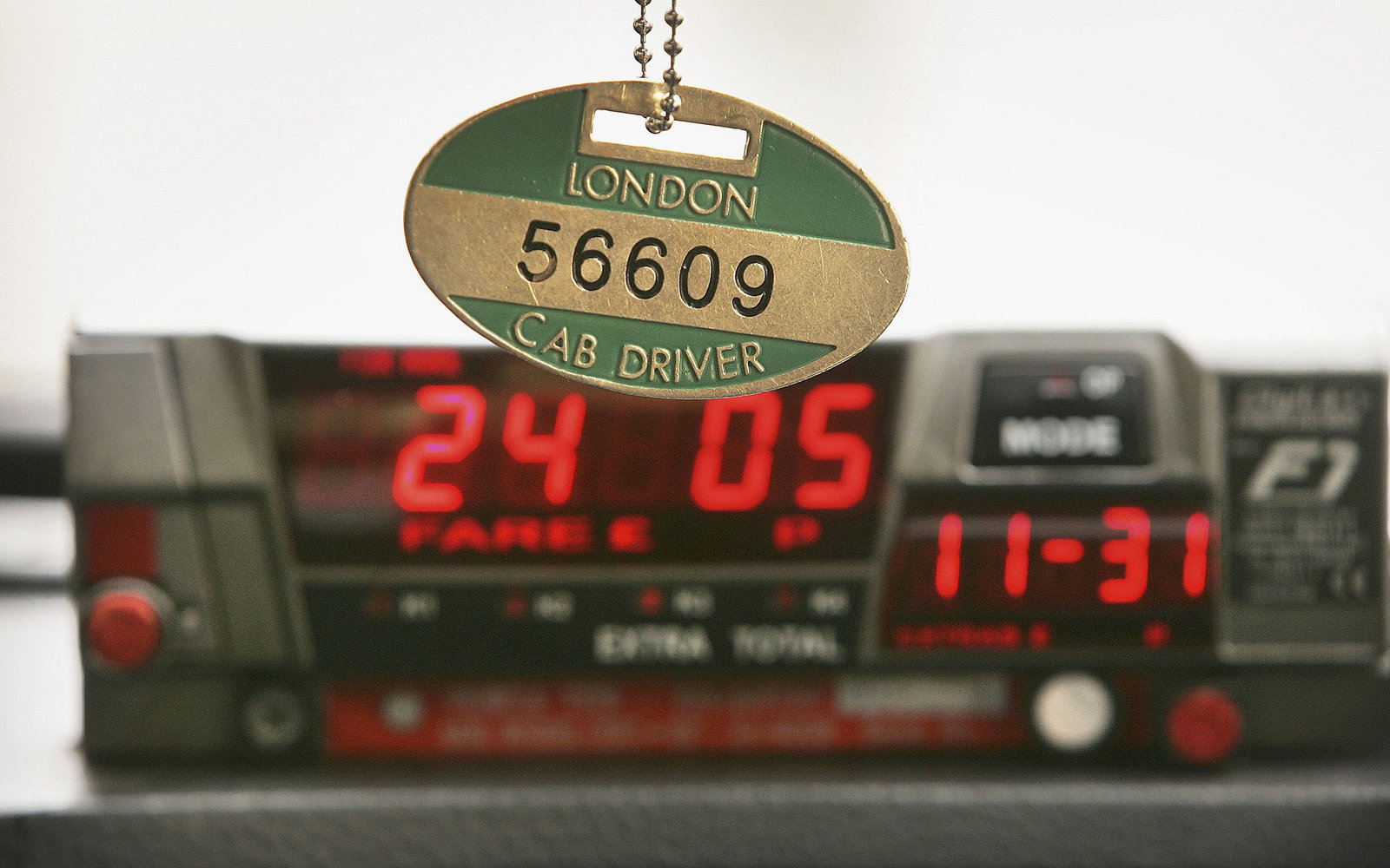 LONDON - MAY 24:  A black taxi cab driver displays his licence badge above his fare meter on May 24, 2006 in London. There are over 19,000 licensed taxis in London. To obtain a taxi cab drivers licence every driver must pass a tough examination known as '