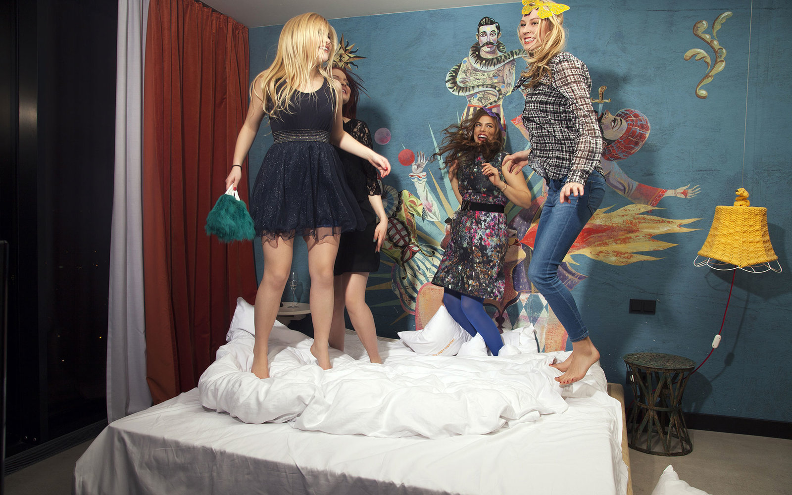Four young women friends dancing on hotel bed