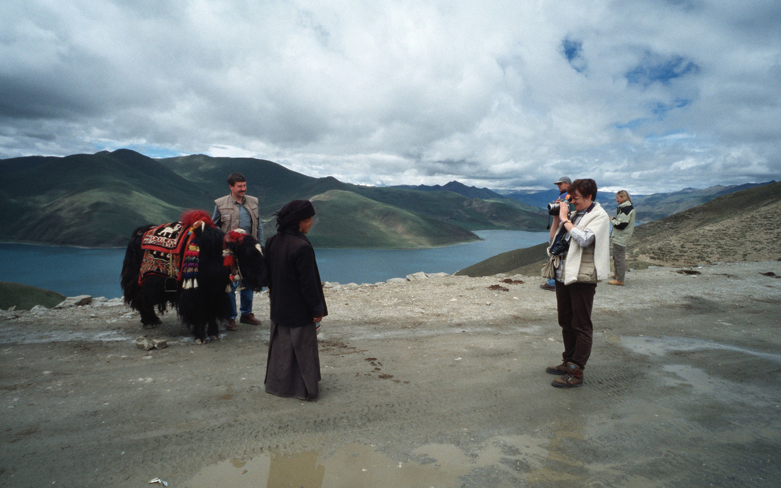 TIBET, CHINA - 2000/08/01: A Tibetan nomad poses for a photo as a group of tourists takes a break on the road from Lhasa to Kathmandu.. (Photo by Yvan Cohen/LightRocket via Getty Images)