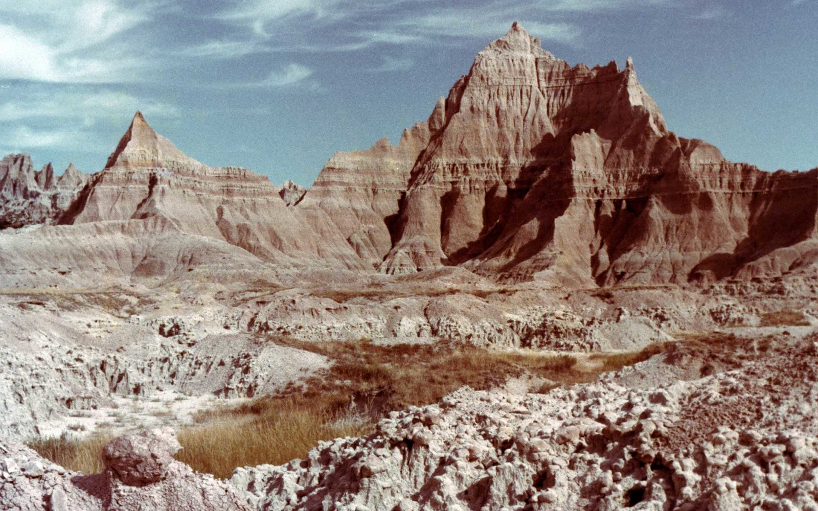 Eroded Peaks with blue sky and whispy clouds, Badlands National Park, South Dakota, 1975. (Photo by Smith Collection/Gado/Getty Images).