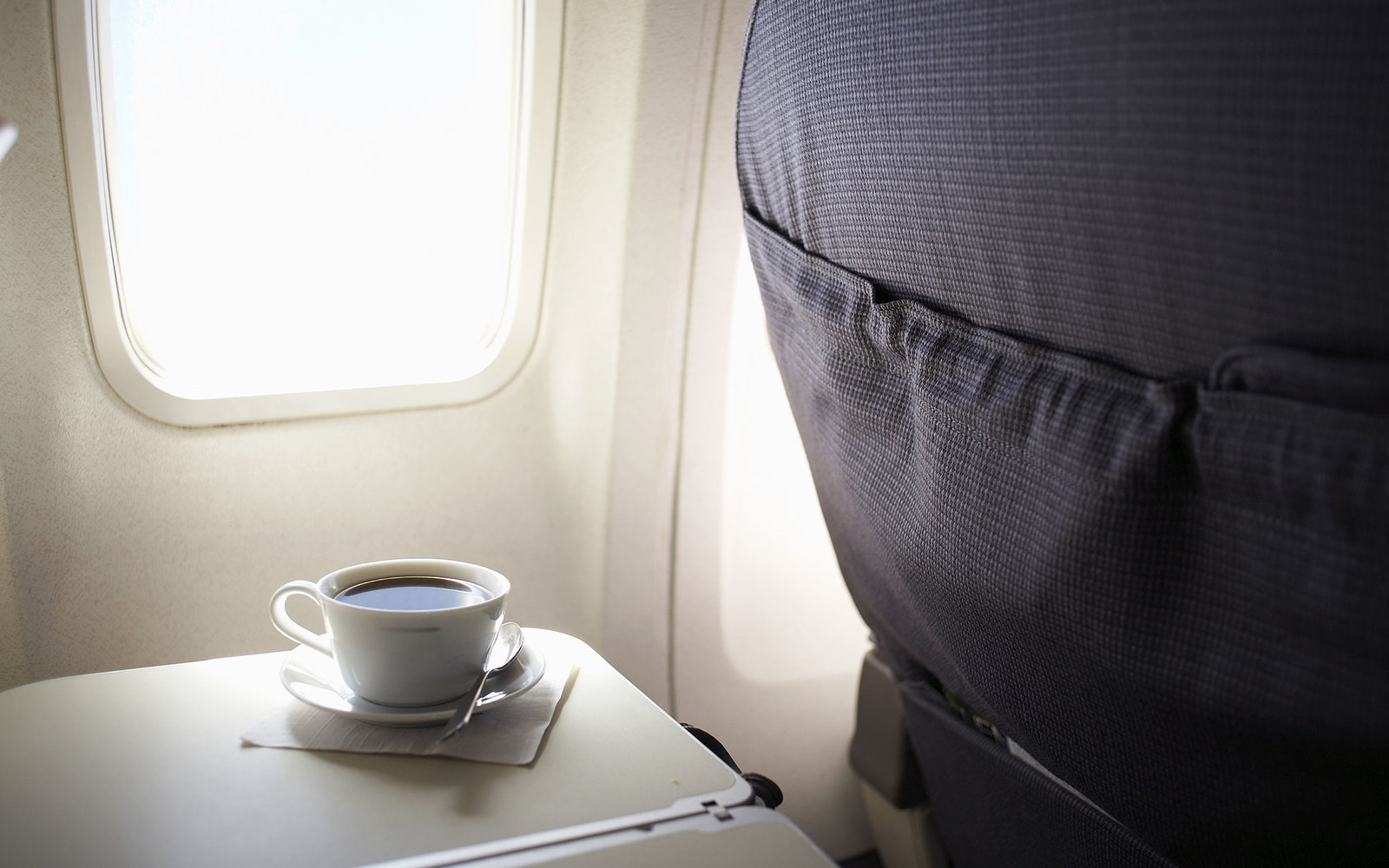 Cup of coffee on airplane tray table by window, elevated view
