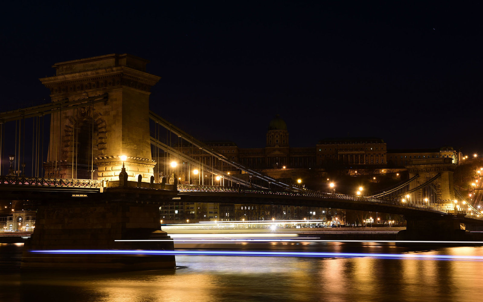 Picture taken on March 19, 2016 shows the oldest Hungarian bridge, the 'Chain Bridge' with the Buda Castle on top of the Castle Hill of Budapest downtown after the city lights were switched off to mark the annual Earth Hour event.