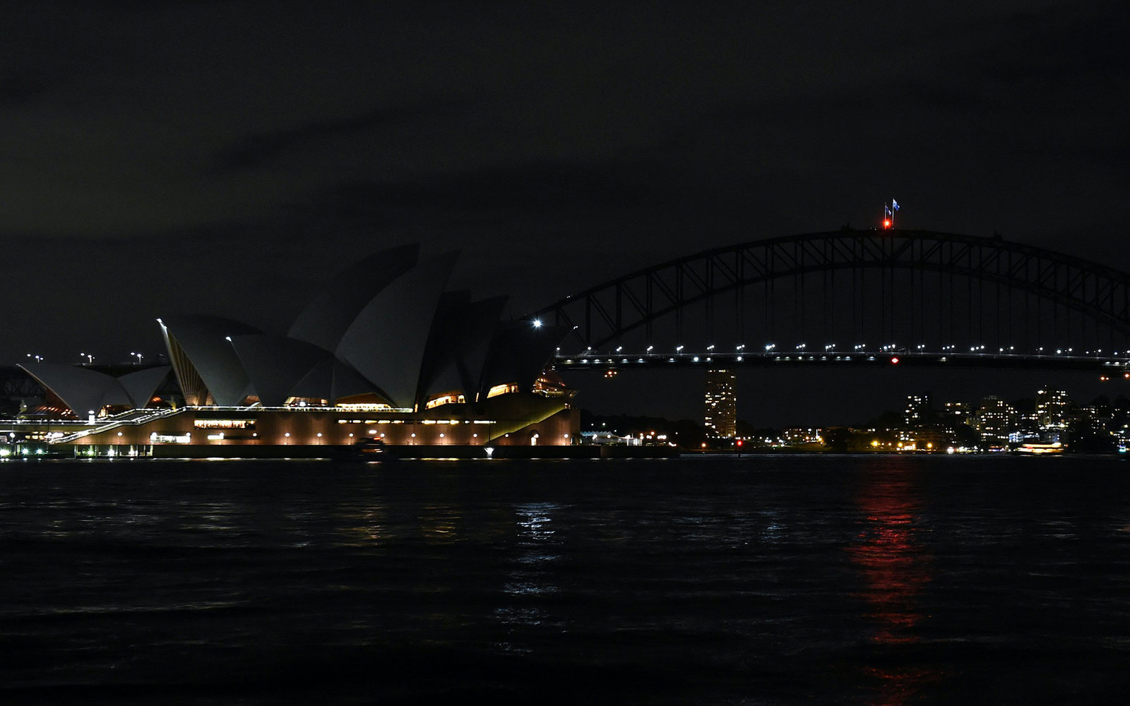 This picture taken on March 19, 2016 shows Australia's iconic Sydney Opera House and Harbour Bridge with the lights turned off during the Earth Hour campaign in Sydney.