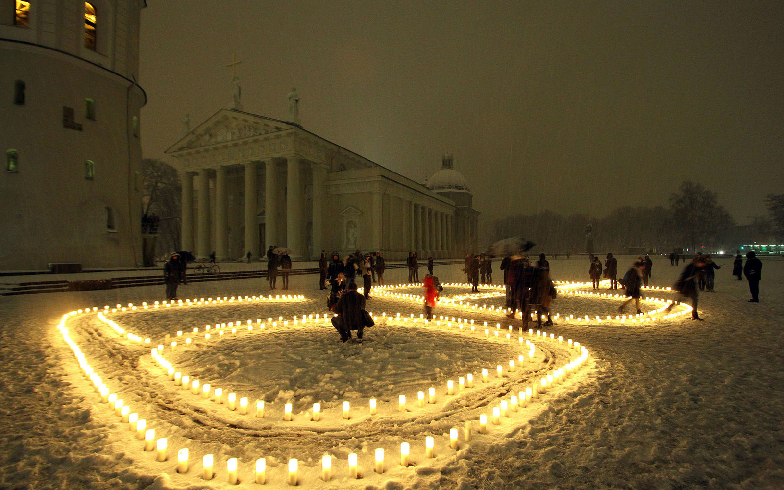 People attend a candle light vigil at the Vilnius Cathedral as it stands unlit during Earth Hour in Vilnius on March 19, 2016.