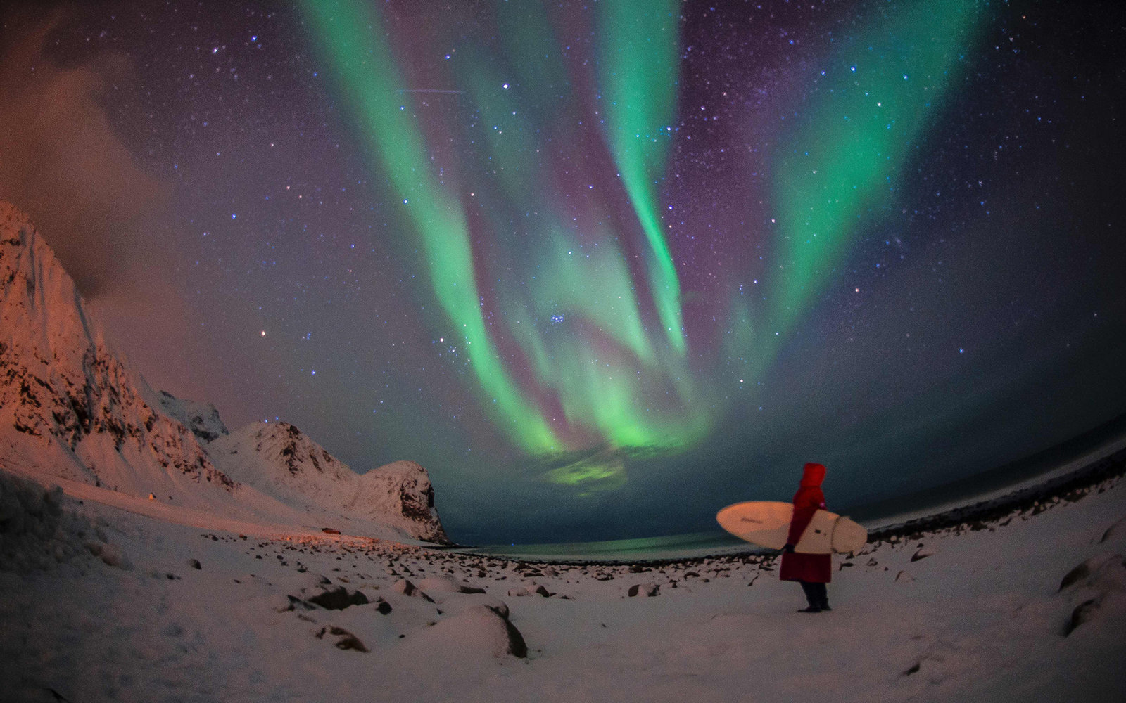 70f2e459503b A surfer looks at northern lights ( aurora borealis ) at the snow covered  beach of