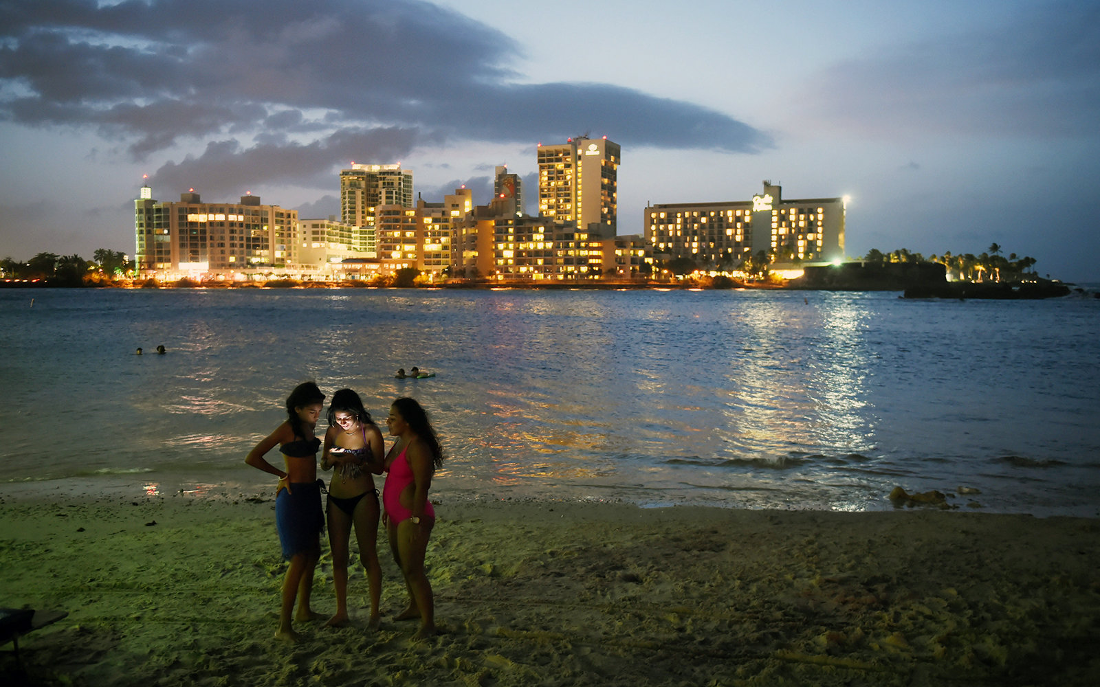 SAN JUAN, PUERTO RICO - JULY 04: Beach goers are illuminated by a phone on Saturday July 04, 2015 in San Juan, Puerto Rico. Many people headed to local beaches and waterways to spend the Fourth of July. (Photo by Matt McClain/ The Washington Post via Gett