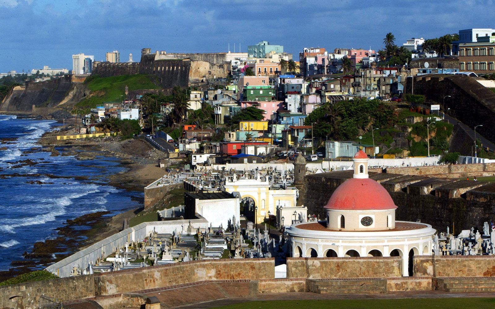 SAN JUAN, PUERTO RICO- APRIL 25: The cupola of San Juan Cemetary as well as colorful homes sit next to the ocean April 25, 2004 in Old San Juan, the original capital city of San Juan, Puerto Rico. The old city is a historic district of seven square blocks