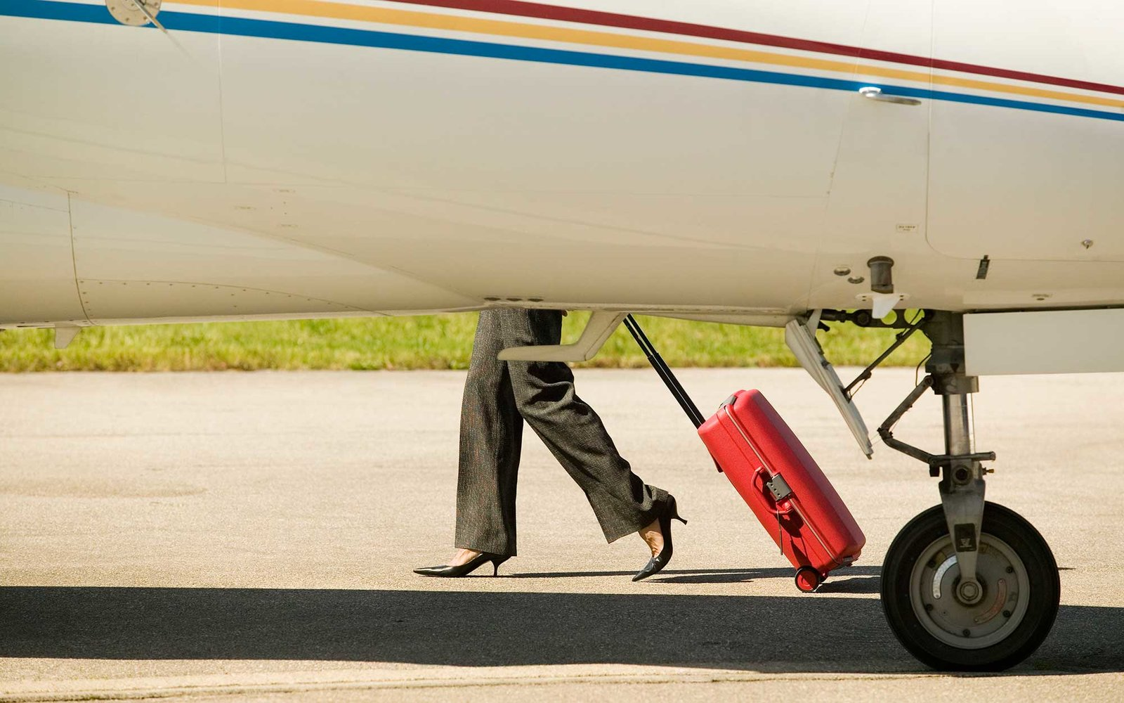 Woman walking with suitcase behind airplane