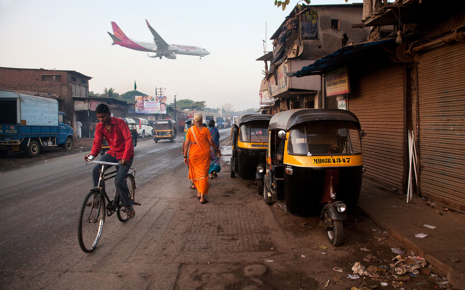 Plane landing at Mumbai International Airport next to slums.