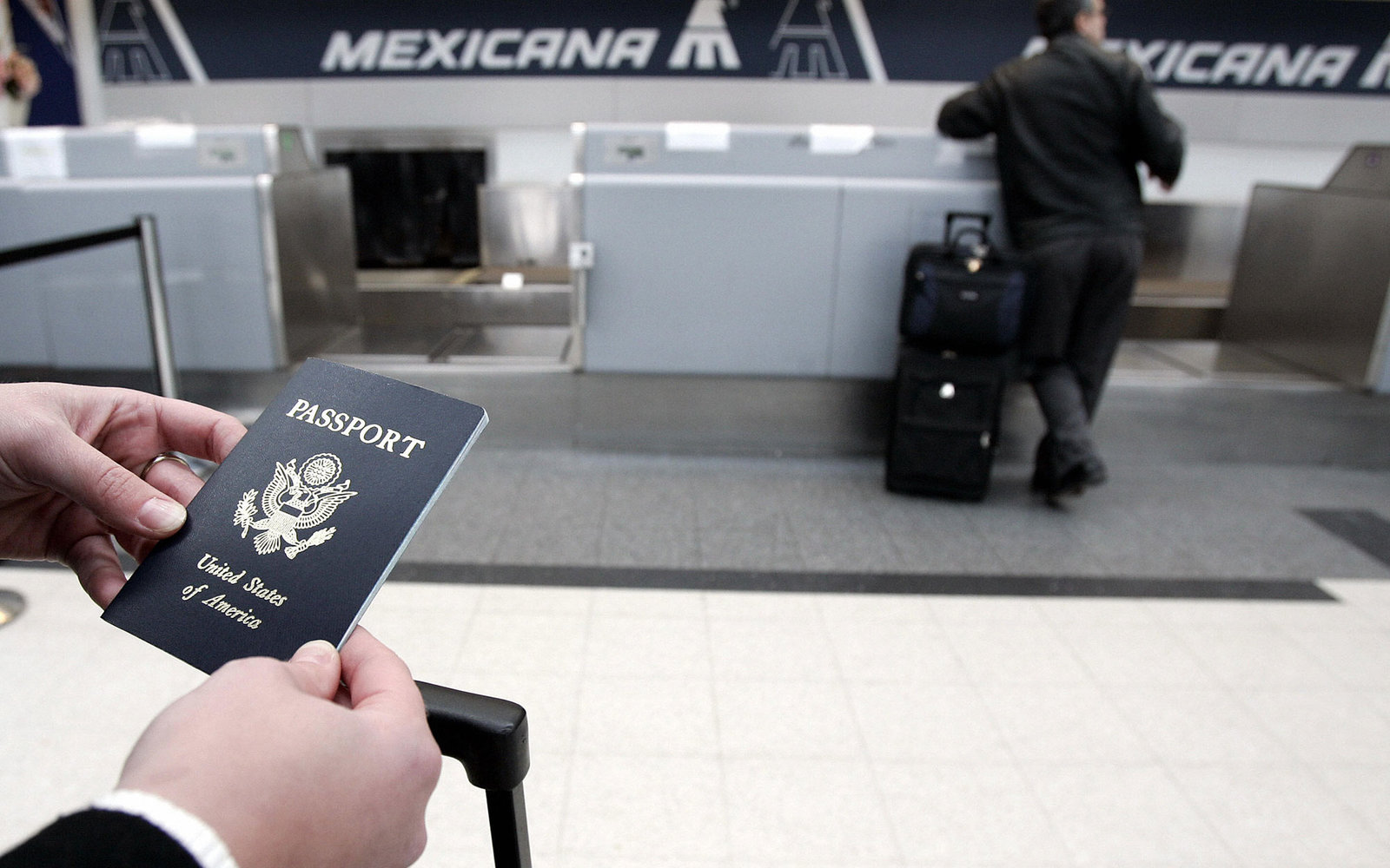 Chicago, UNITED STATES:  A passenger waits in line with her passport 23 January, 2007 before her Mexicana Air flight out of Chicago O'Hare International airport in Chicago, Illinois.  As of 23 January, all Americans, Mexicans, Canadians and Bermudians tra