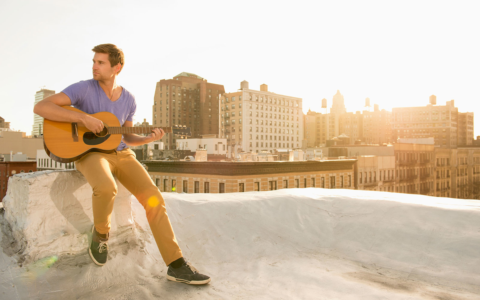 Caucasian man playing guitar on urban rooftop